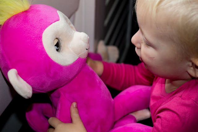 A pink cuddly monkey with a toddler