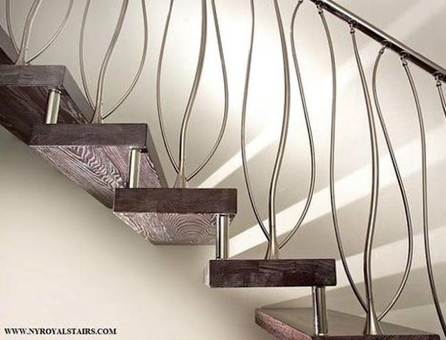 Escalera interior con barandilla de metal elaborado con formas orgánicas