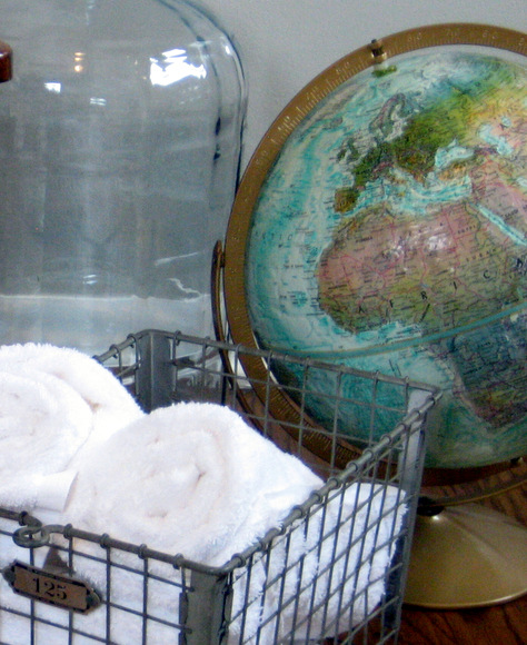 This vintage globe pairs well with the rustic bin for towels.