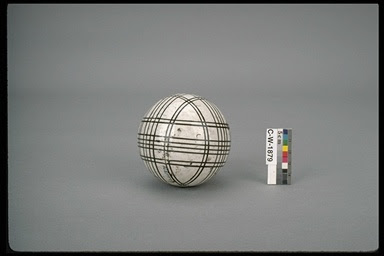 A somewhat dingy white sphere with thin black lines circling it in two directions, to form an irregular checked pattern. Beside it is a card with blocks of several colors.