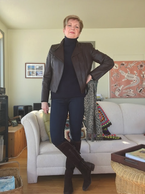 woman in brown boots and leather jacket, jeans and a navy sweater, holding a scarf standing in front of a sofa