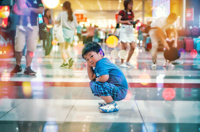 Child kneeling in the middle of the floor in a mall