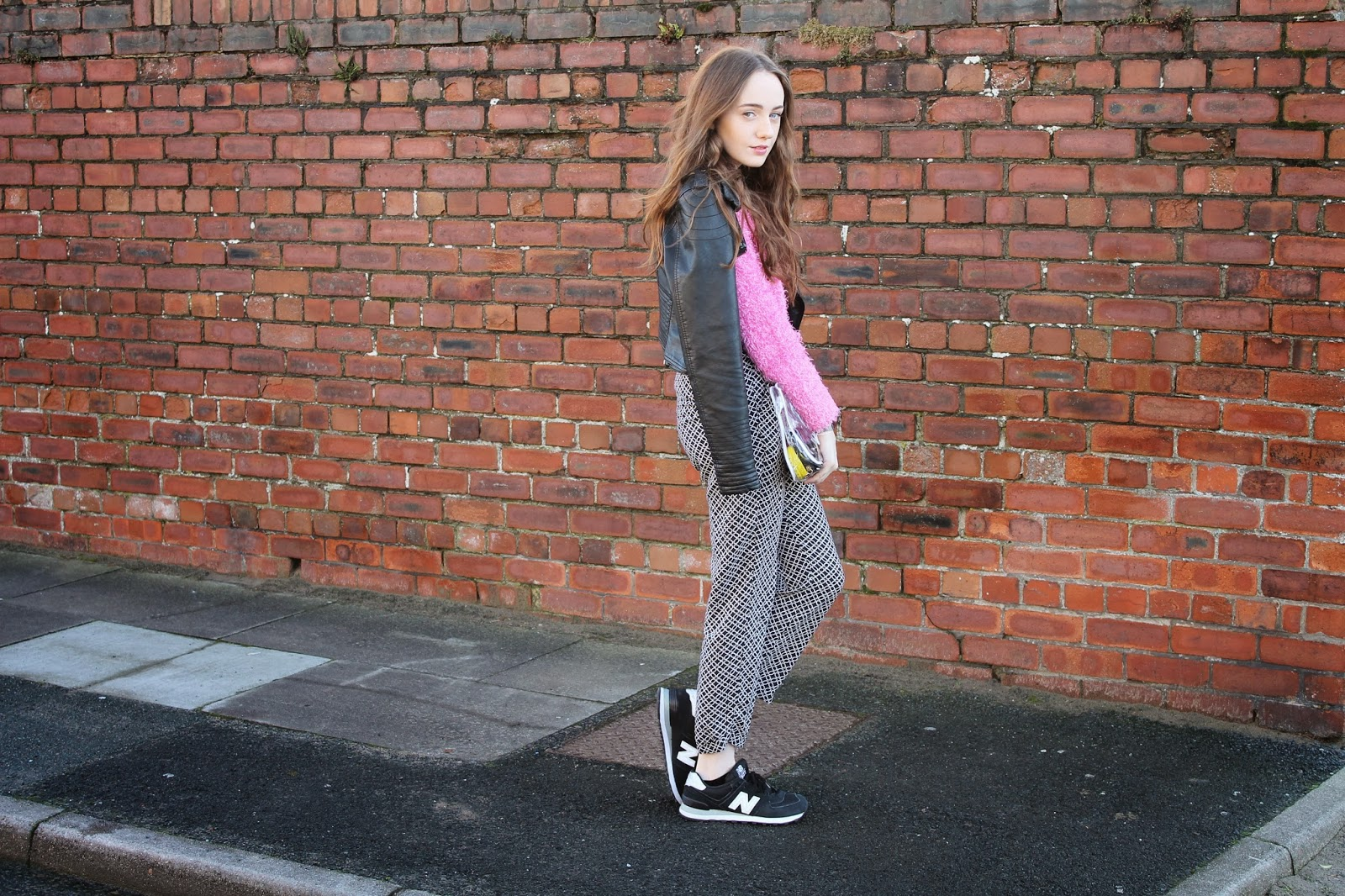 blogger wearing new balances trainers, black and white new balance 540s, leather jacket worn over shoulders, see-through bag, clear clutch, pink fluffy primark jumper, monochrome pants