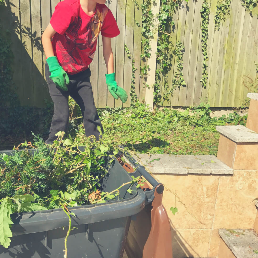 "LP, a 9 year old boy - stands in a garden wearing green gardening gloves. He is helping with gardening as part of his chores. Image for ""Why I give my children chores""."