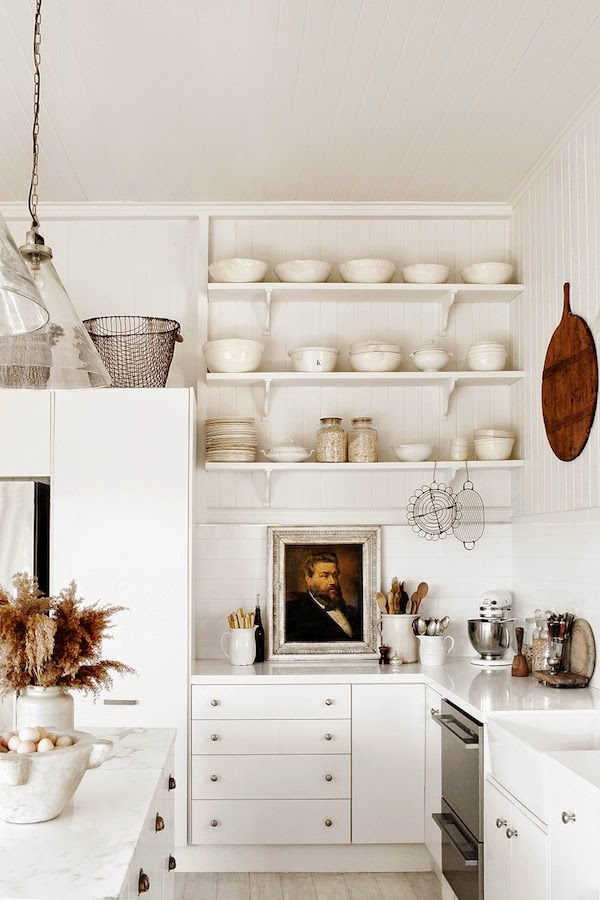 Kara Rosenlund white farmhouse country kitchen with oil painting portrait on counter and open shelving. #whitekitchen #moderncountry #vintagestyle