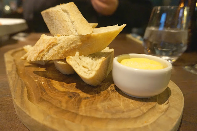 Sourdough bread and pot of butter on wooden board