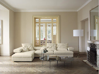 Contemporary Family Room with White Modern Sofa Bed and some White Cushions near the Rounded Tables