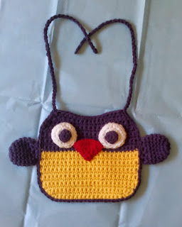 Owl Bib: the bottom half (owl body) is yellow and the top half (owl head) is purple. The bib has a purple border and purple ties.  Purple wings are attached to the side.  The appliquéd eyes are big round circles with smaller purple circles inside. The appliquéd beak is a red triangle.