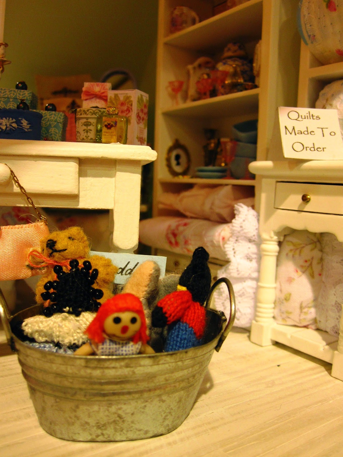 Modern miniature shabby chic shop display of soft toys in a tin tub on the floor, with a display of quilts on cream shelves behind.