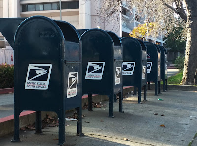 5 U.S. Postal mailboxes aligned in a row on a drive-by sidewalk