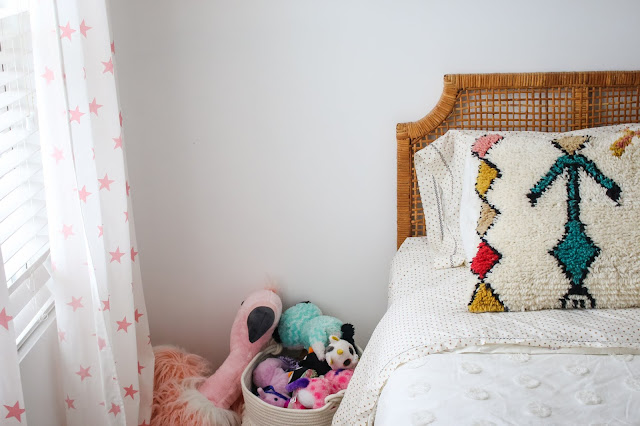A boho shared girls' room with the sweetest rattan headboards