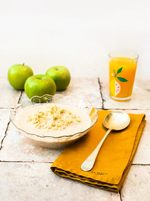 Apple & Cinnamon Overnight Oats in a glass bowl beside a glass of orange juice