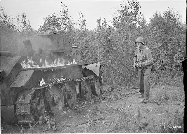 A Finnish soldier advances past a burning Soviet tank, apparently a BT-7, 5 August 1941 worldwartwo.filminspector.com