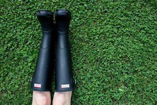 View of a person's legs in knee-high black boots lying on a field of clover - Photo by Sydney Rae on Unsplash