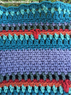 FREE crochet pattern. Colorful baby blanket in seed or moss stitch. By April Garwood of Banana Moon Studio.