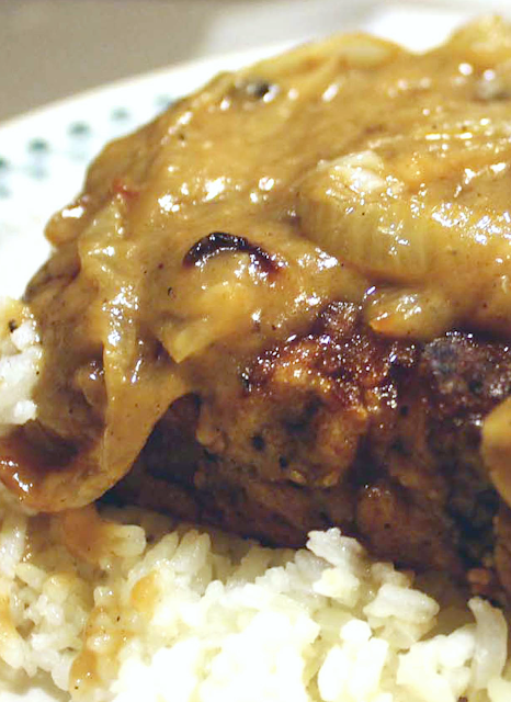 Fried Pork Chops with Onion Gravy over a bed of cooked rice