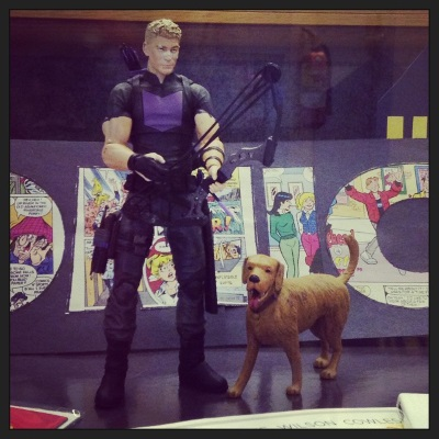 An action figure of Pizza Dog, a sorta-golden retriever, stands next to an action figure of Clint Barton, a blond white guy wearing black and purple duds and carrying a bow and arrow.