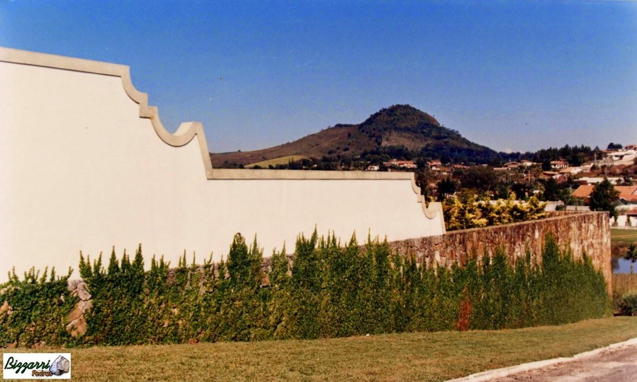 Construção do muro de arrimo com pedra para formar um grande platô para construção da piscina e a construção da residência.