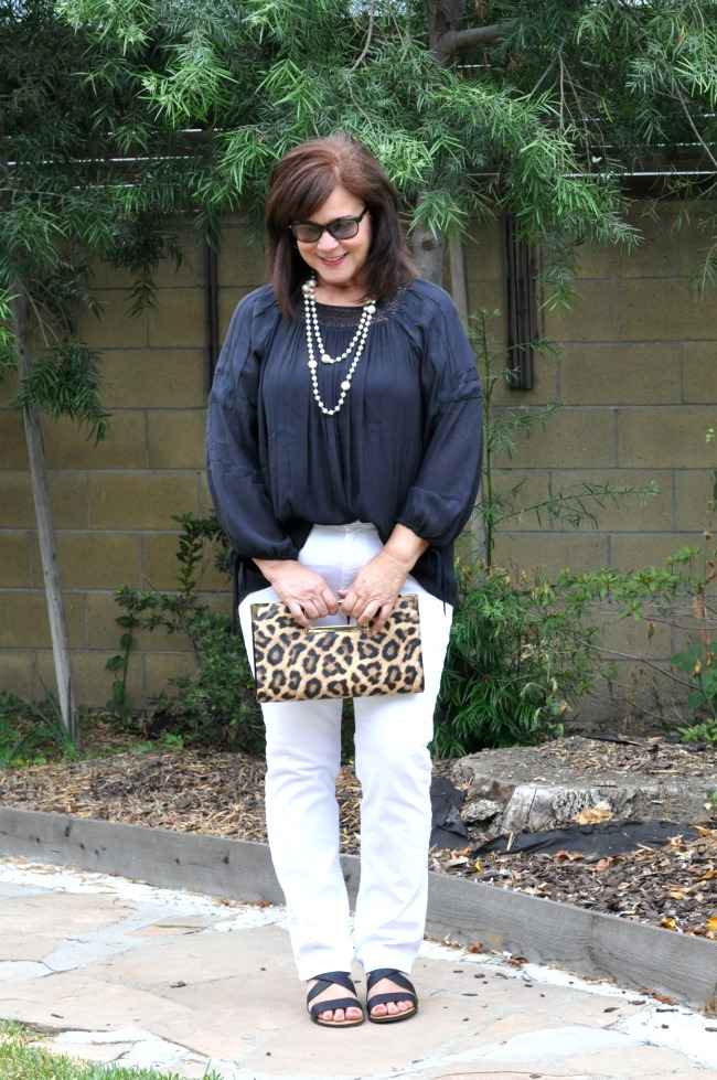 white jeans and black top with leopard purse