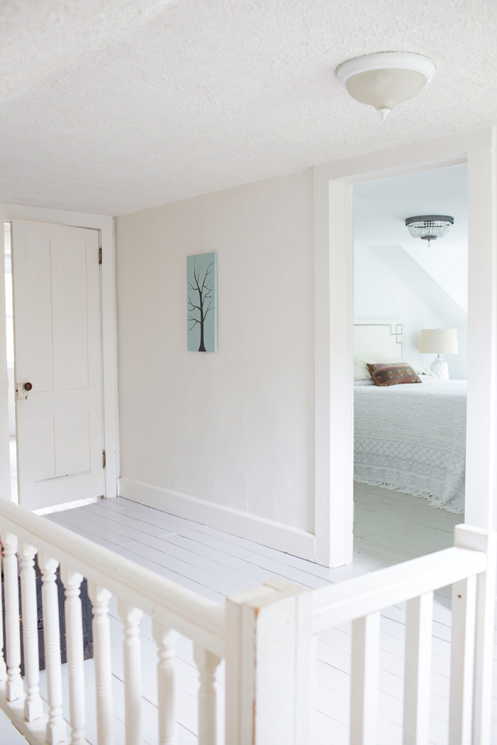 Open upstairs hallway painted white staged minimally to sell