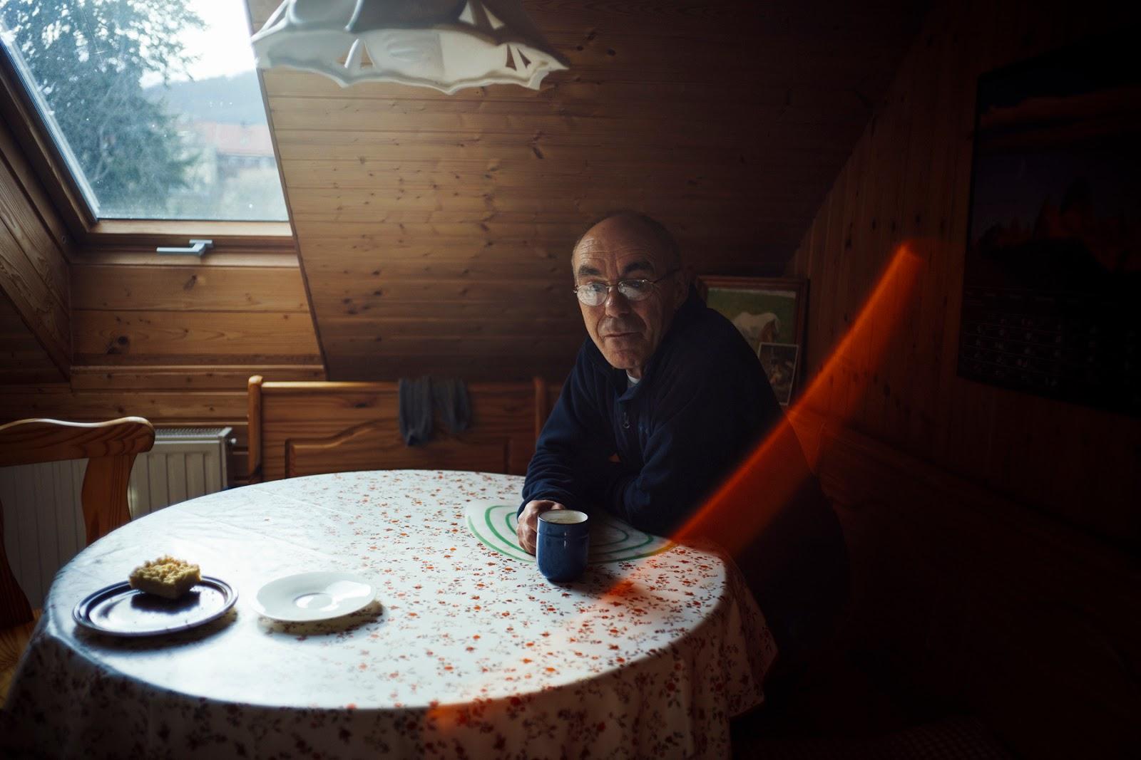 Ein älterer Mann sitzt an einem runden Tisch und hat eine Kaffeetasse in der Hand