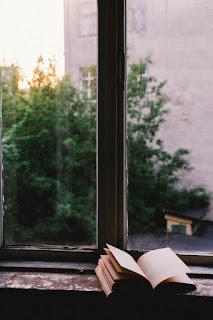 o carte la o fereastră pe o vreme mohorâtă - foto de  John-Mark Smith - unsplash.com
