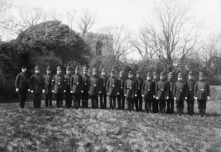 A black and white group portrait of 20 Victorian police constables in uniform, standing in a line in the middle of a grassy area, with a hedgerow and church tower in the background.