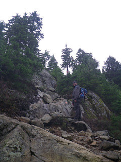A photo of one person on bare rock with trees in the background. There are two orange trail markers, one on the rock and one on a tree farther along.