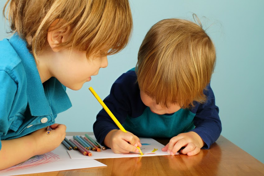 Two young brothers drawing together
