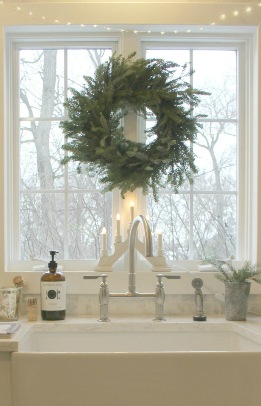 Fresh green holiday wreath on window above farmhouse sink