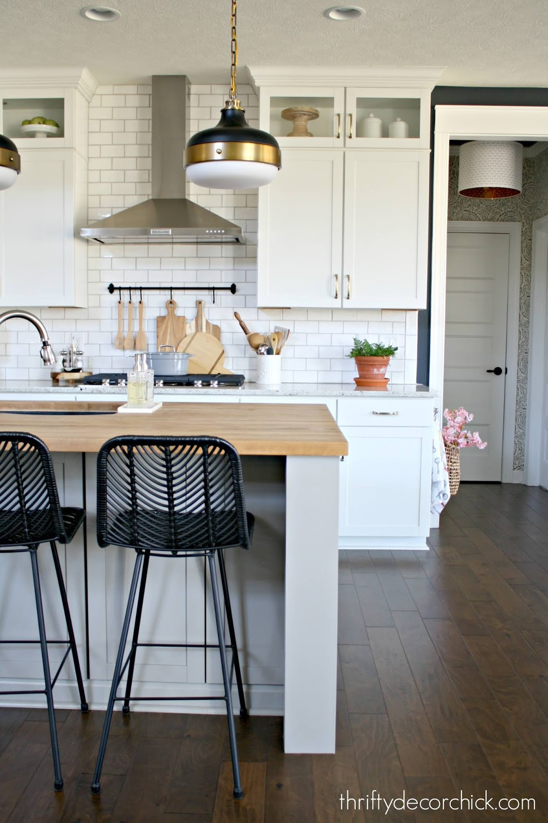 Light gray island, white kitchen cabinets, black stools