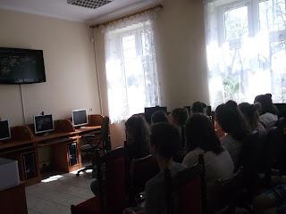 Uczniowie oglądają film edukacyjny - widok na plecy uczestników spotkania