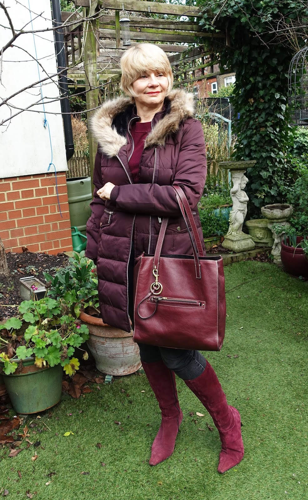 Burgundy fur trimmed parka from Oasis worn with burgundy suede boots and jeans.