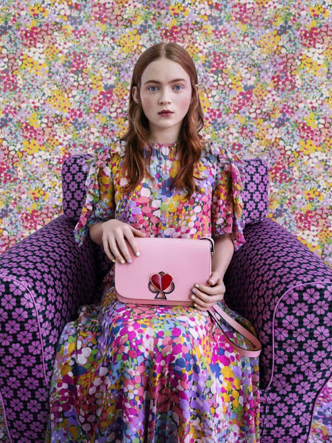 Sadie Sink in a flower dress, holding a pink Kate Spade handbag by Tim Walker