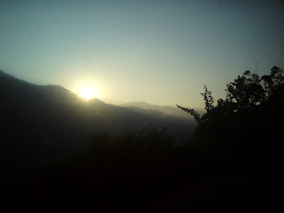 Sun peeping out from behind the clouds just before sunset  in the Garhwal Himalayas
