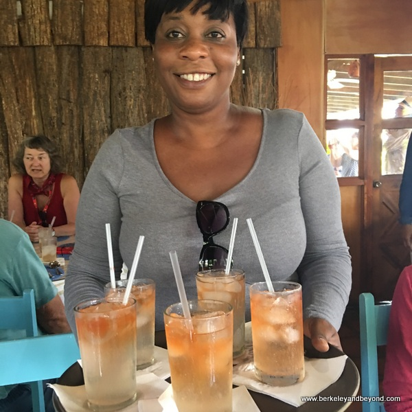 tour guide Monica pitches in serving drinks at Blue Crab Restaurant in Scarborough, Tobago