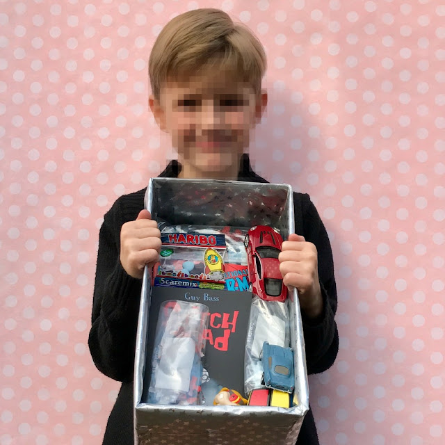 a 7 year old boy (pixelated face) holding a shoebox containing toy cars and books, pink background with white spots.
