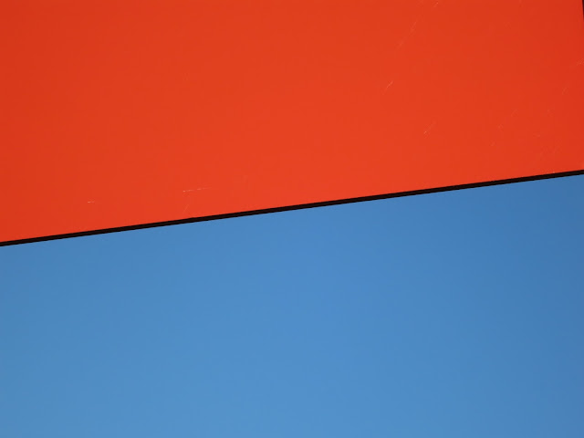 The red of the back of a No-Entry sign against the blue of the sky