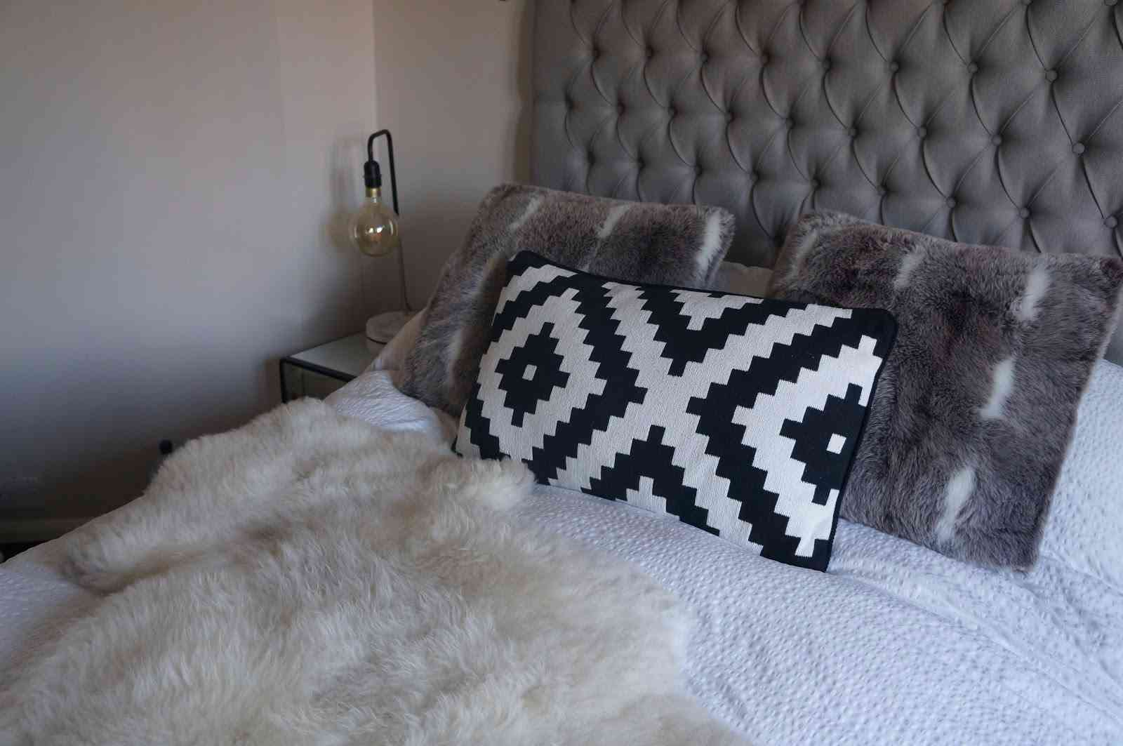 cosy grey bed with black and white cushion and fluffy throw