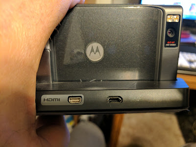 Motorola Droid X in a charging dock with microUSB port oriented correctly (broader edge down), according to practices in the USA.