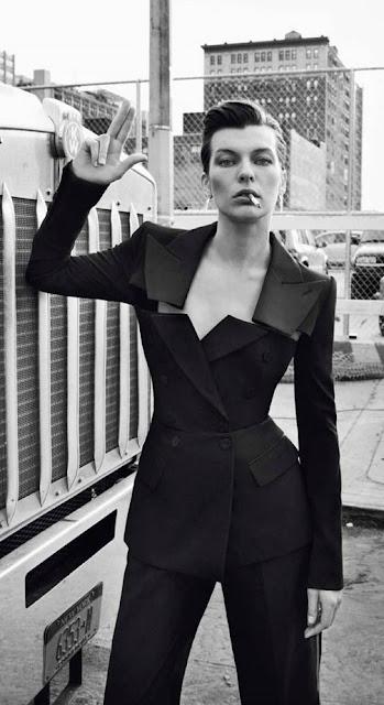 Actress Milla Jovovich smoking, wearing a black pants suit,