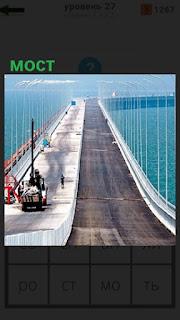 происходит строительство моста, стоит кран и люди рядом