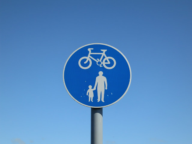 Blue sign to say walkers and bikes allowed. Against blue sky.