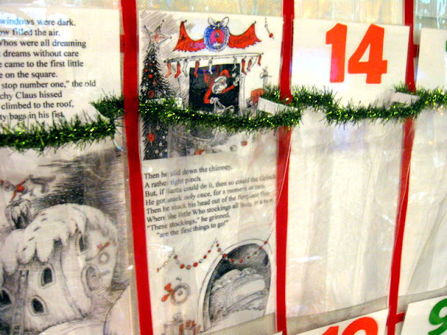 A close up photo of the homemade Grinch advent calendar showing  parts of the story in  each window of a plastic shoe organizer