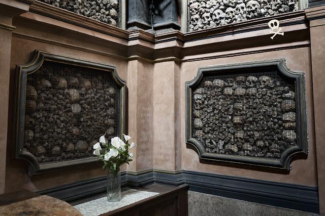 Hornacinas abiertas en la pared rellenas de huesos en composición artística.