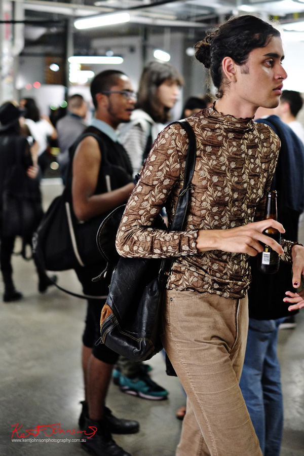 Black nail polish, woman's sheer brown long-sleeve embroidered top over light brown jeans worn as menswear. Spring Fashion Ambushed by Street Fashion Sydney. Photographed by Kent Johnson.