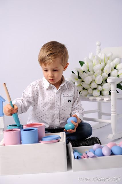 Mały elegancki chłopiec na sesji fotograficznej maluje pędzel pisanki wielkanocne