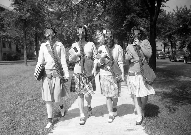 Looking ahead to the possibility that gas masks may some day be a necessary part of their ensemble, these University of Detroit students were trying out masks in a practice drill on the campus on June 23, 1942. Hidden behind the masks, which they soon learned to wear with a minimum of discomfort, are, from left: Mary Turner, Helen Williams, Evelyn Buss and Joan Joliet.