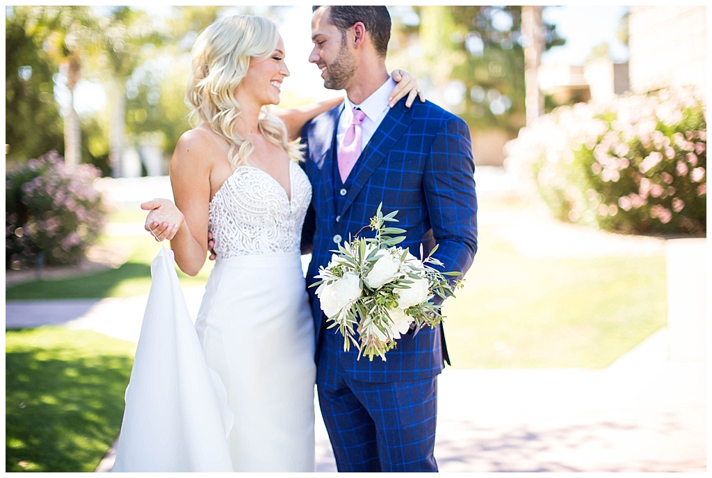 bride in two piece wedding dress and groom in custom blue suit