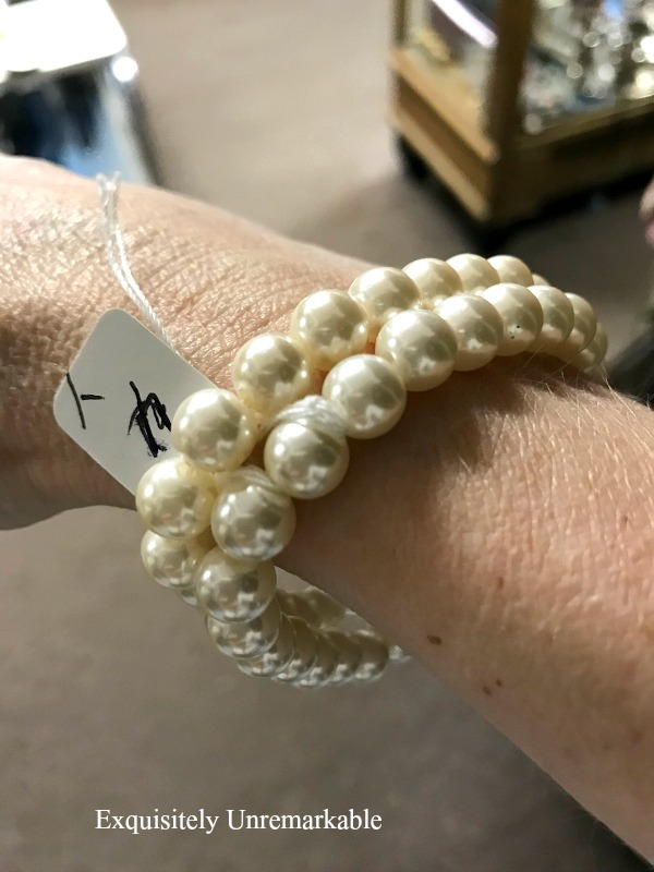 Pearl Bracelets on a wrist with a $4 price tag